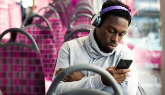 Image of man with headphones looking at phone